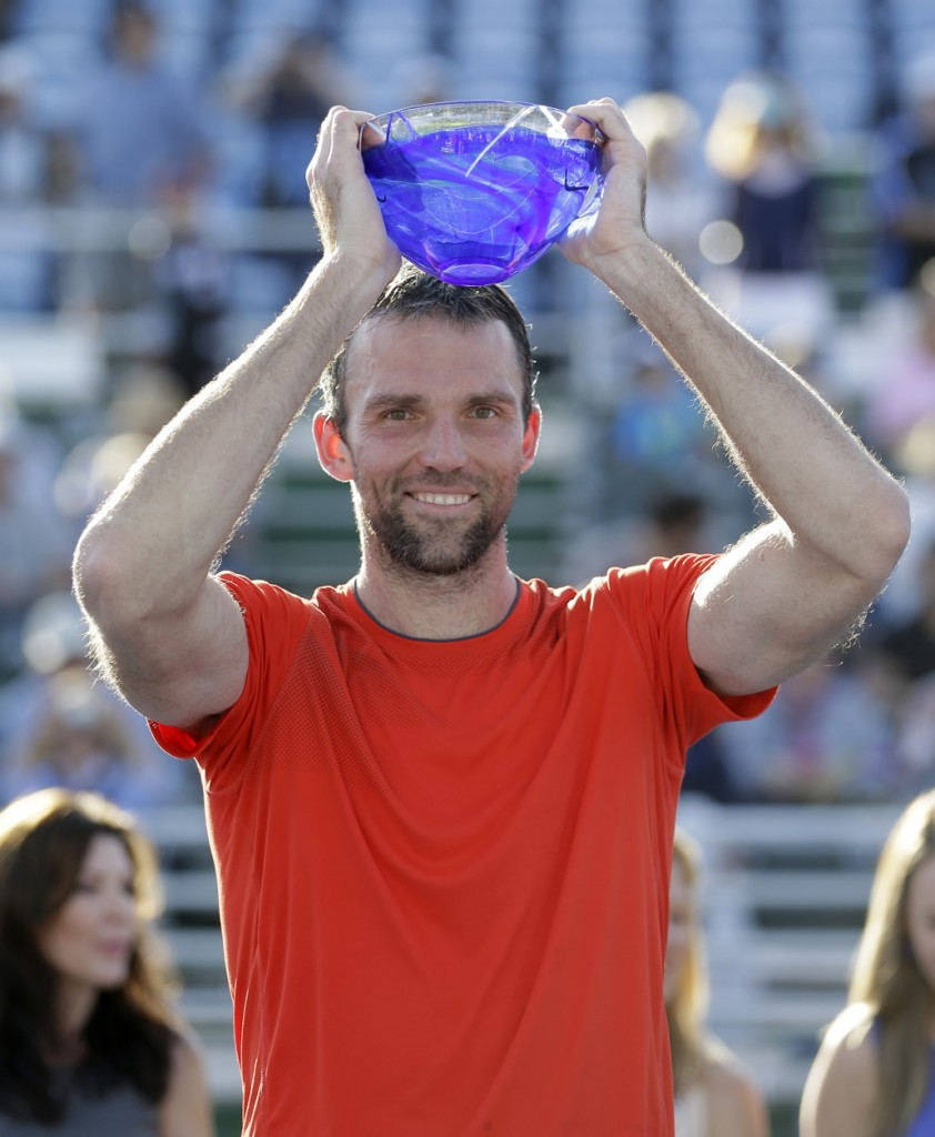 Ivo Karlovic, of Croatia, raises his trophy after winning 6-3, 6-3 over Donald Young during the final tennis match at the Delray Beach Open, in Delray Beach, Fla., Sunday, Feb. 22, 2015. (AP Photo/Alan Diaz)