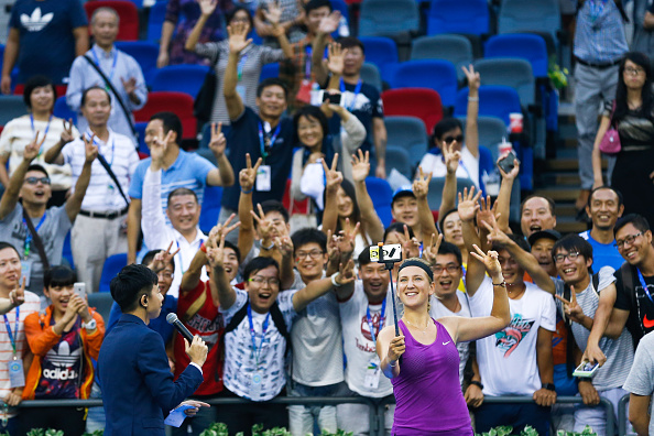 WUHAN, CHINA - SEPTEMBER 27:  (CHINA OUT) Victoria Azarenka of Belarus takes selfie with fans after a match in the first round of 2015 Wuhan Open at Optics Vally International Tennis Center on September 27, 2015 in Wuhan, Hubei Province of China.  (Photo by ChinaFotoPress/ChinaFotoPress via Getty Images)