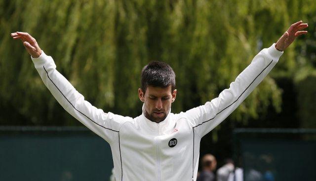Novak Djokovic of Serbia stretches before a practice session at Wimbledon in London June 23, 2013.  REUTERS/Stefan Wermuth  (BRITAIN - Tags: SPORT TENNIS) - RTX10Y0Z