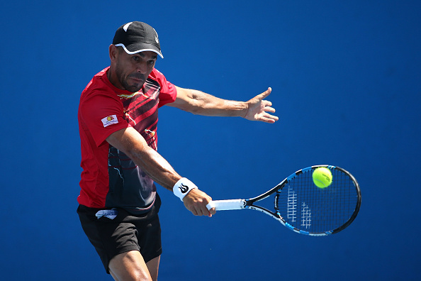 MELBOURNE, AUSTRALIA - JANUARY 18:  Victor Estrella Burgos of Dominican Republic plays a backhand in his first round match against Daniel Brands of Germany during day one of the 2016 Australian Open at Melbourne Park on January 18, 2016 in Melbourne, Australia.  (Photo by Jack Thomas/Getty Images)