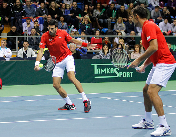 KRALJEVO, SERBIA - MARCH 07: Novak Djokovic (L) and Nenad Zimonjic of Serbia in action against  Marin Draganja and Franko Skugor of Croatia during their men's double match on the day two of the Davis Cup match between Serbia and Croatia on March 07, 2015 in Kraljevo, Serbia. (Photo by Srdjan Stevanovic/Getty Images)