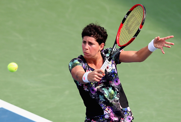 DUBAI, UNITED ARAB EMIRATES - FEBRUARY 17:  Carla Suarez Navarro of Spain plays a backhand in her match against Caroline Garcia of France during day three of the WTA Dubai Duty Free Tennis Championship at the Dubai Duty Free Stadium  on February 17, 2016 in Dubai, United Arab Emirates.  (Photo by Francois Nel/Getty Images)