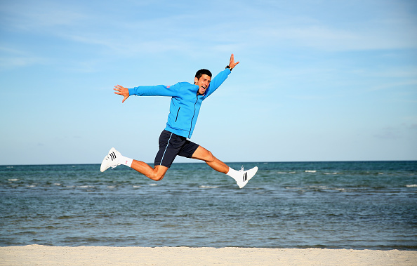 KEY BISCAYNE, FL - APRIL 05:  Novak Djokovic of Serbia leaps in the air on Crandon Park beach after his three set victory against Andy Murray of Great Britain in the mens final during the Miami Open Presented by Itau at Crandon Park Tennis Center on April 5, 2015 in Key Biscayne, Florida.  (Photo by Clive Brunskill/Getty Images)
