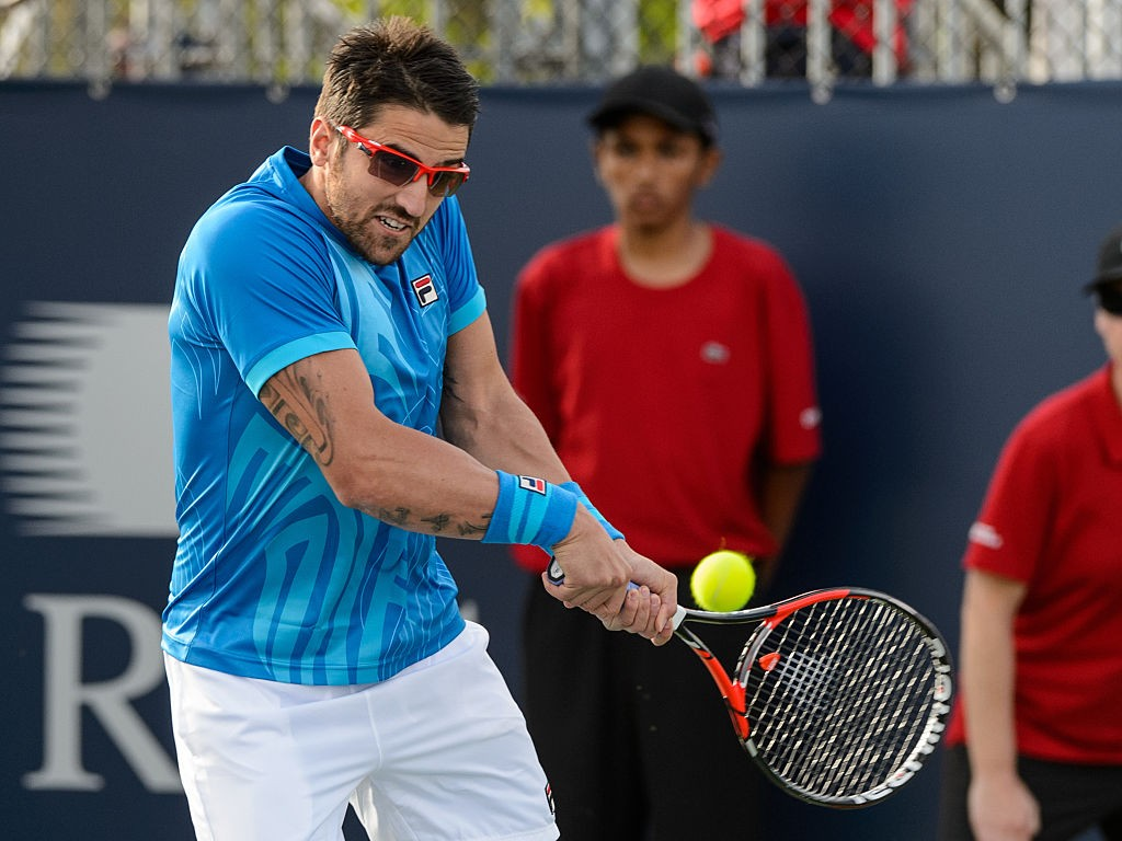 MONTREAL, ON - AUGUST 12:  Janko Tipsarevic of Serbia hits a return against Rohand Bopanna of India and Florin Mergea of Romania during day three of the Rogers Cup at Uniprix Stadium on August 12, 2015 in Montreal, Quebec, Canada.  (Photo by Minas Panagiotakis/Getty Images)
