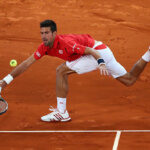 MADRID, SPAIN - MAY 06:  Novak Djokovic of Serbia stretches for a forehand in his match against Milos Raonic of Canada during day seven of the Mutua Madrid Open tennis tournament at the Caja Magica on May 06, 2016 in Madrid, Spain.  (Photo by Julian Finney/Getty Images)