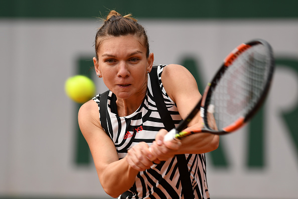 PARIS, FRANCE - MAY 23:  Simona Halep of Romania plays a backhand during the Women's Singles first round match against Nao Hibino of Japan on day two of the 2016 French Open at Roland Garros on May 23, 2016 in Paris, France.  (Photo by Dennis Grombkowski/Getty Images)