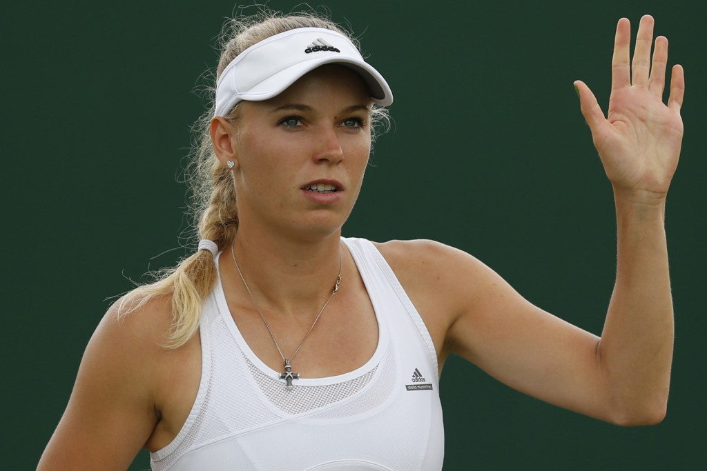 Caroline Wozniacki of Denmark waves after her first round match against Shahar Peer of Israel at the All England Lawn Tennis Championships in Wimbledon, London, Tuesday, June 24, 2014. (AP Photo/Ben Curtis)