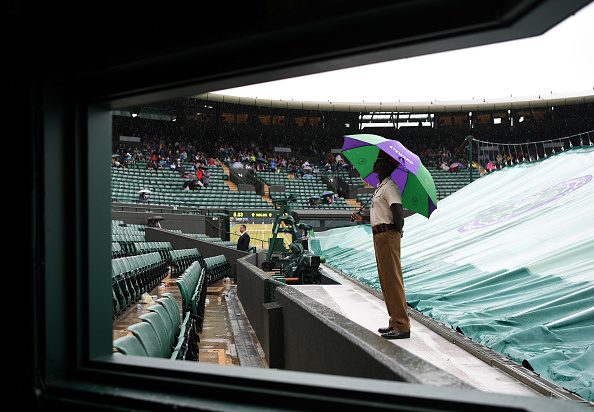 LONDON, ENGLAND - JUNE 28:  A service steward looks on from under an umbrella on court one during day two of the Wimbledon Lawn Tennis Championships at the All England Lawn Tennis and Croquet Club on June 28, 2016 in London, England.  (Photo by Shaun Botterill/Getty Images)