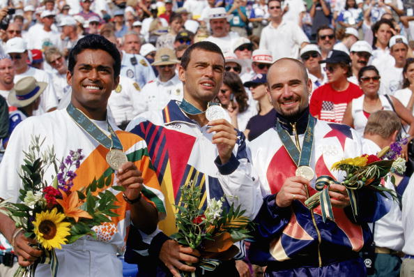 ATLANTA - AUGUST 3:  Tennis men's singles finalist, left, bronze medal winner Leander Paes of India, center, silver medal winner Sergi Bruguera of Spain and, right, gold winner Andre Agassi celebrate during the XXVI Olympic Games at the Stone Mountain Tennis Center on August 3, 1996 in Atlanta, Georgia. (Photo by Gary M. Prior/Getty Images)