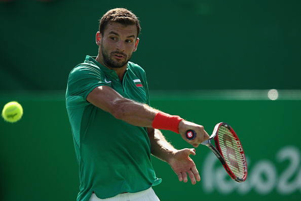 RIO DE JANEIRO, BRAZIL - AUGUST 06:  Grigor Dimitrov of Bulgaria in action against Marin Cilic of Croatia in the men's first round on Day 1 of the Rio 2016 Olympic Games at the Olympic Tennis Centre on August 6, 2016 in Rio de Janeiro, Brazil.  (Photo by Julian Finney/Getty Images)