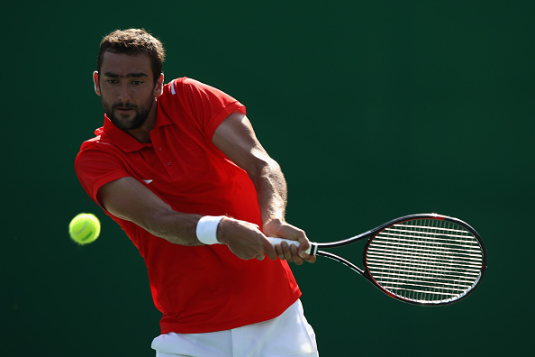 RIO DE JANEIRO, BRAZIL - AUGUST 06:  Marin Cilic of Croatia in action against Grigor Dimitrov of Bulgaria in the men's first round on Day 1 of the Rio 2016 Olympic Games at the Olympic Tennis Centre on August 6, 2016 in Rio de Janeiro, Brazil.  (Photo by Julian Finney/Getty Images)