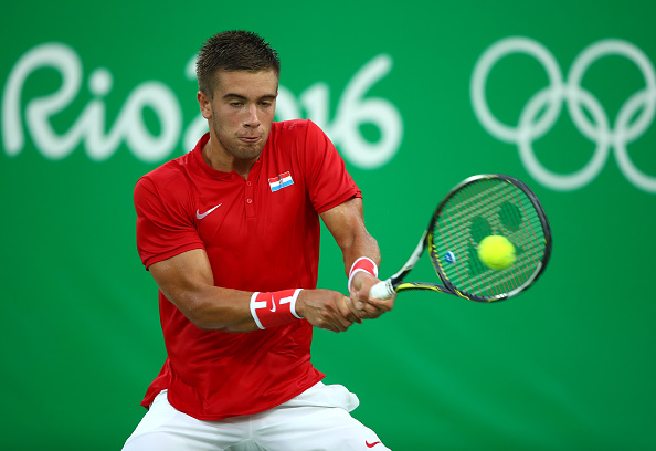 RIO DE JANEIRO, BRAZIL - AUGUST 06:  Borna Coric of Croatia plays a backhand against Gilles Simon of France in their first round match on Day 1 of the Rio 2016 Olympic Games at the Olympic Tennis Centre on August 6, 2016 in Rio de Janeiro, Brazil.  (Photo by Clive Brunskill/Getty Images)
