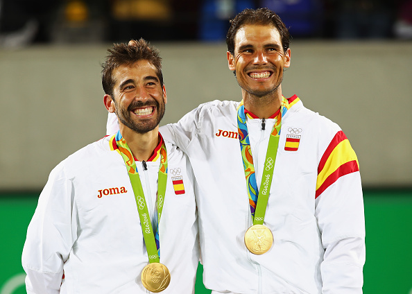 RIO DE JANEIRO, BRAZIL - AUGUST 12:  (L-R) Gold medalists Rafael Nadal and Marc Lopez of Spain celebrate on the podium after the Men's Doubles competition on Day 7 of the Rio 2016 Olympic Games at the Olympic Tennis Centre on August 12, 2016 in Rio de Janeiro, Brazil.  (Photo by Clive Brunskill/Getty Images)