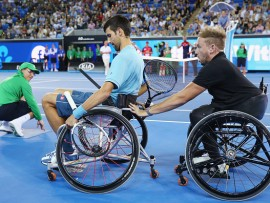 MELBOURNE, AUSTRALIA - JANUARY 11:  Novak Djokovic of Serbia is helped along by Australian  wheelchair tennis player Dylan Alcott before playing with him during 'A Night with Novak' at Margaret Court Arena on January 11, 2017 in Melbourne, Australia.  (Photo by Michael Dodge/Getty Images)