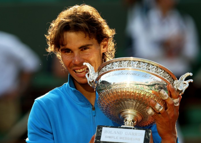 PARIS, FRANCE - JUNE 05: Champion Rafael Nadal of Spain bites the trophy following his record equalling sixth victory during the men's singles final match between Rafael Nadal of Spain and Roger Federer of Switzerland on day fifteen of the French Open at Roland Garros on June 5, 2011 in Paris, France. (Photo by Clive Brunskill/Getty Images)