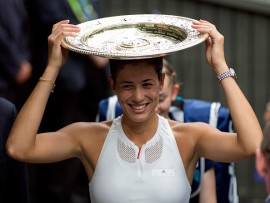 Garbine Muguruza balances the trophy on her head as she walks off court after beating Venus Williams in the Ladie's Singles final on day twelve of the Wimbledon Championships at The All England Lawn Tennis and Croquet Club, Wimbledon. (Photo by Steven Paston/PA Images via Getty Images)