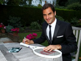 "Roger Federer of Switzerland celebrates his Wimbledon record with an exclusive commemorative ""8"" Wilson tennis racket after his victory against Marin Cilic of Croatia on day thirteen of the Wimbledon Lawn Tennis Championships at the All England Lawn Tennis and Croquet Club on July 16, 2017 in London, England."