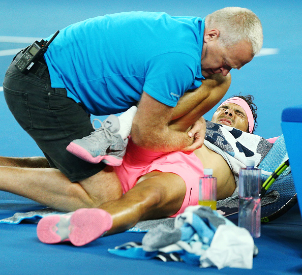 MELBOURNE, AUSTRALIA - JANUARY 23:  Rafael Nadal of Spain is attended to by a trainer as he has injury time out in his quarter-final match against Marin Cilic of Croatia on day nine of the 2018 Australian Open at Melbourne Park on January 23, 2018 in Melbourne, Australia.  (Photo by Michael Dodge/Getty Images)