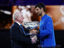 MELBOURNE, AUSTRALIA - JANUARY 14:  Novak Djokovic presents Rod Laver with the Norman Brookes Challenge Cup during the 50th anniversary celebration for Australian Open and Rod Laver's second Grand Slam during day one of the 2019 Australian Open at Melbourne Park on January 14, 2019 in Melbourne, Australia.  (Photo by Julian Finney/Getty Images)