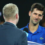 MELBOURNE, AUSTRALIA - JANUARY 25:  Novak Djokovic of Serbia speaks with Jim Courier on court after winning his men's semi final match against Lucas Pouille of France during day 12 of the 2019 Australian Open at Melbourne Park on January 25, 2019 in Melbourne, Australia.  (Photo by Michael Dodge/Getty Images)