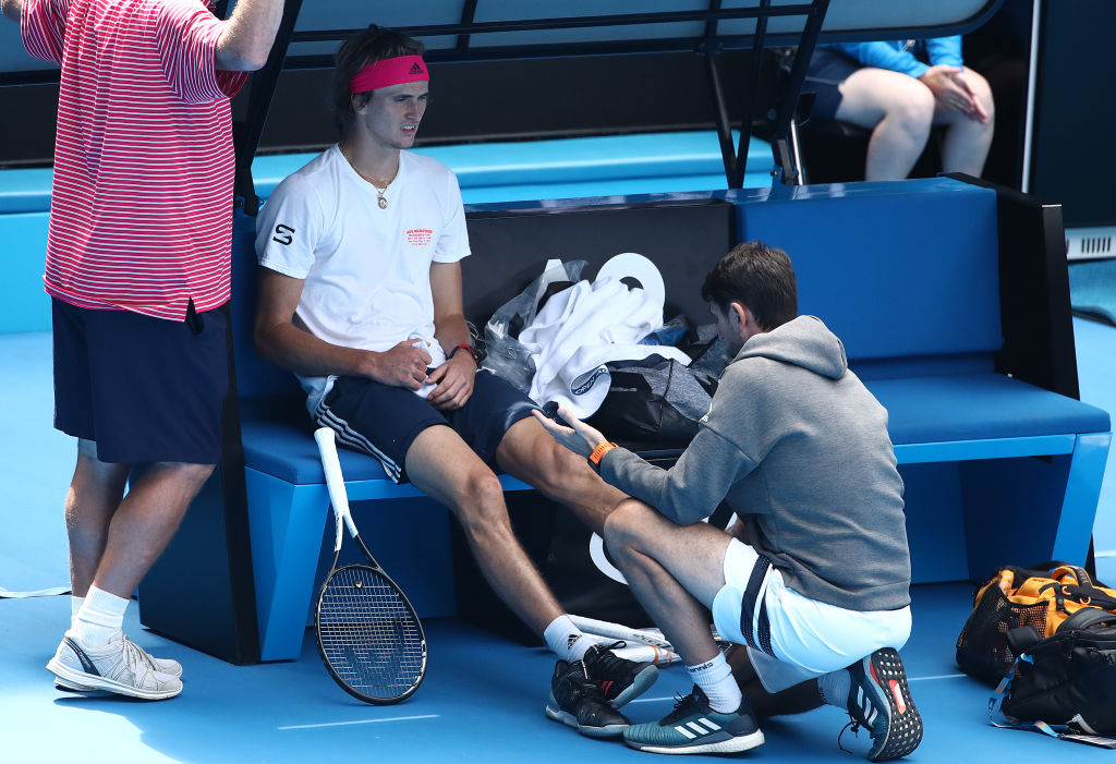 MELBOURNE, AUSTRALIA - JANUARY 10: Alexander Zverev of Germany is treated for an injury before leaving the court injured after his exhibition match ahead of the 2019 Australian Open at Melbourne Park on January 10, 2019 in Melbourne, Australia. (Photo by Scott Barbour/Getty Images)