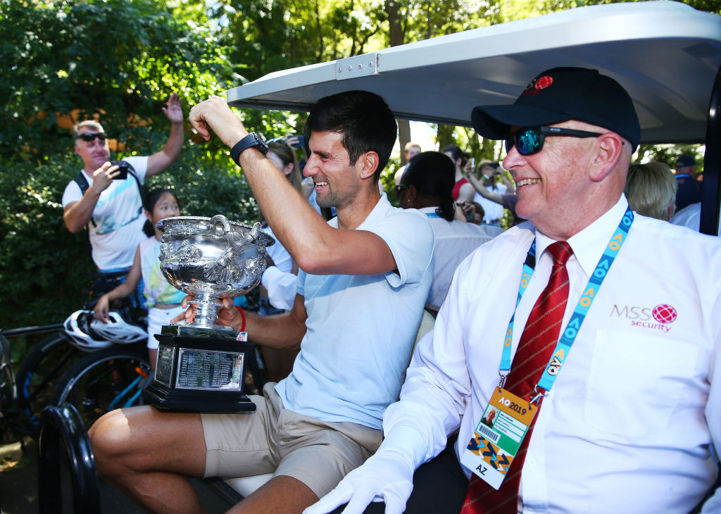 MELBOURNE, AUSTRALIA - JANUARY 28: Novak Djokovic of Serbia leaves on a golf buggy with the Norman Brookes Challenge Cup after winning the 2019 Australian Open at Picnic Point, Royal Botanical Gardens on January 28, 2019 in Melbourne, Australia. (Photo by Michael Dodge/Getty Images)