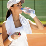 sporty woman drinking water after tennis training