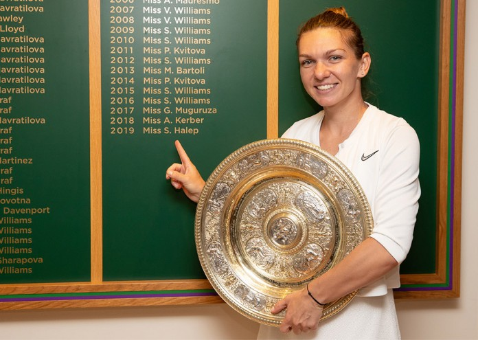 Simona Halep (ROU) stands next to the Champions board with the Venus Rosewater Dish after winning the Ladies' Singles final. The Championships 2019. Held at The All England Lawn Tennis Club, Wimbledon. Day 12 Saturday 13/07/2019: Credit: AELTC/Ben Queenborough