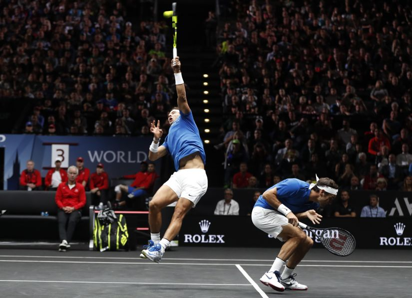 Europe's Roger Federer, right, crouches as his teammate Rafael Nadal, left, returns a ball to World's Jack Sock and Sam Querrey during their Laver Cup doubles tennis match in Prague, Czech Republic, Saturday, Sept. 23, 2017. (AP Photo/Petr David Josek)