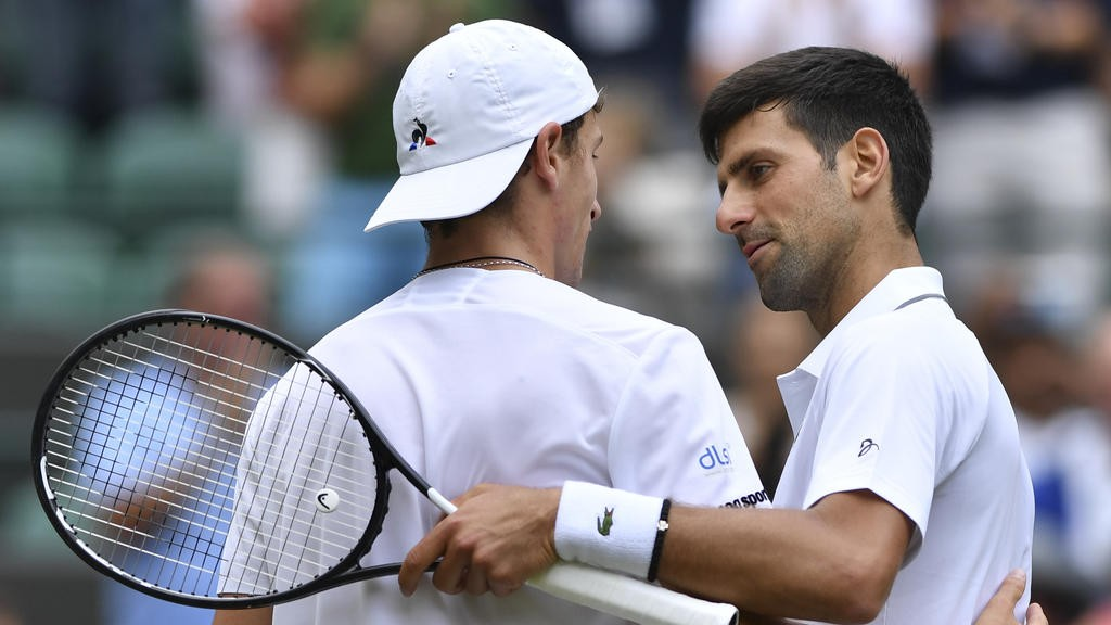 Serbia's Novak Djokovic (R) shakes hands with France's Ugo Humbert (L) after Djokovic won their men's singles fourth round match on the seventh day of the 2019 Wimbledon Championships at The All England Lawn Tennis Club in Wimbledon, southwest London, on July 8, 2019. (Photo by GLYN KIRK / AFP) / RESTRICTED TO EDITORIAL USE