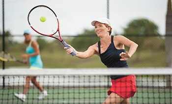 young woman playing Doubles tennis, hitting a forehand volley
