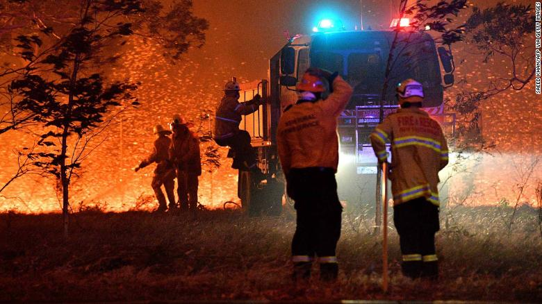 Firefighters hose down trees as they battle against bushfires around the town of Nowra in the Australian state of New South Wales on December 31, 2019. - Thousands of holidaymakers and locals were forced to flee to beaches in fire-ravaged southeast Australia on December 31, as blazes ripped through popular tourist areas leaving no escape by land. (Photo by SAEED KHAN / AFP) (Photo by SAEED KHAN/AFP via Getty Images)