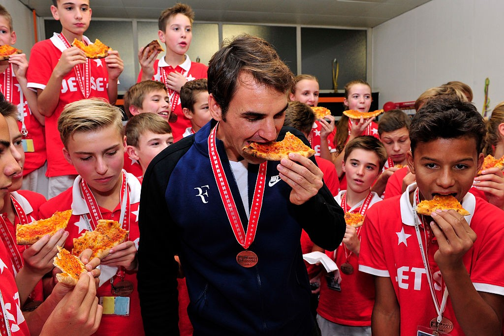 BASEL, SWITZERLAND - NOVEMBER 01:  Roger Federer (C) of Switzerland hands out pizza as he celebrates with the ball boys winning the final match of the Swiss Indoors ATP 500 tennis tournament against Rafael Nadal of Spain at St Jakobshalle on November 1, 2015 in Basel, Switzerland  (Photo by Harold Cunningham/Getty Images)